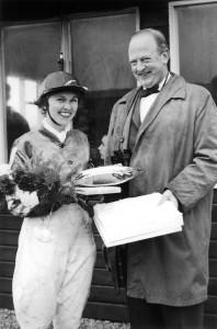 """Margit Engelund vandt det første """"Silver Blaze"""" galopløb i 1963 med hesten Kara Mustapha. Her modtager hun blomster samt ærespræmien af Henry Lauritzen, BSI."""